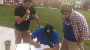 Junior member Aaron Botts and sophomore member Will McClure assist sophomore member Eder Sosa with his homework in back circle.